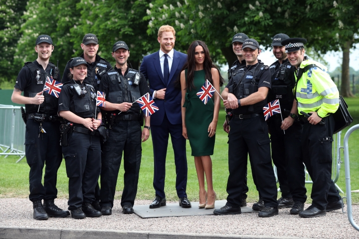 Police officers pose with the Madame Tussauds' wax figures of Prince Harry and Meghan Markle as they are paraded along the Long Walk ahead of the royal wedding this weekend, in Windsor, England, Wednesday, May 16, 2018. (Jonathan Brady/PA via AP)