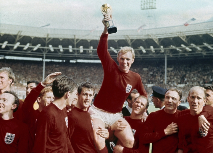 FILE - In this July 30, 1966 file photo, England's soccer captain Bobby Moore, center, is carried by teammates Geoff Hurst, center left, and Ray Wilson as he holds FIFA World Cup after England defeated Germany 4-2 in the final at London's Wembley Stadium. Ray Wilson, the left back for all six of England's games in its World Cup-winning campaign in 1966, has died. He was 83. Former club Huddersfield announced Wilson's death on Wednesday, May 16, 2018. (AP Photo, file)