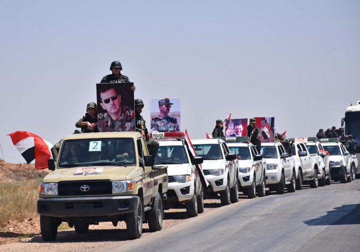 In this photo released Tuesday, May 15, 2018 by the Syrian official news agency, SANA, a convoy of Syrian government forces and police hold portraits of Syrian President Bashar Assad, as they enter a village in the northern countryside of Homs province, Syria. With the latest capitulation by the armed opposition, Syrian government forces have regained control of the largest single swath of land, enabling it to secure roads between the country's three main cities which were before either in rebel hands or the roads leading to them were in the line of fire. (SANA via AP)