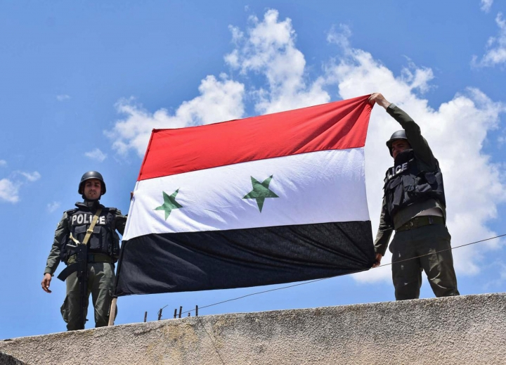 In this photo released Tuesday, May 15, 2018 by the Syrian official news agency, SANA, Syrian government policemen, hold their national flag, after they enter a village in the northern countryside of Homs province, Syria. With the latest capitulation by the armed opposition, Syrian government forces have regained control of the largest single swath of land, enabling it to secure roads between the country's three main cities which were before either in rebel hands or the roads leading to them were in the line of fire. (SANA via AP)