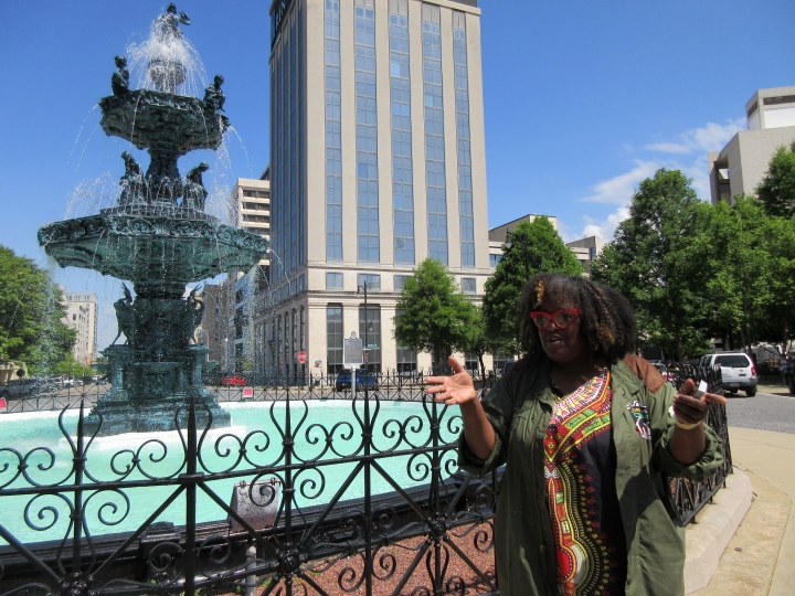 This April 28, 2018 photo shows Michelle Browder standing in front of the Court Square Fountain in Montgomery, Ala., as she leads a tour. Her company, called More Than Tours, takes visitors through the history of the city, from its past as a center of the slave trade and birthplace of the confederacy, through the civil rights era, to the contemporary resurgence of its downtown. (AP Photo/Beth J. Harpaz)