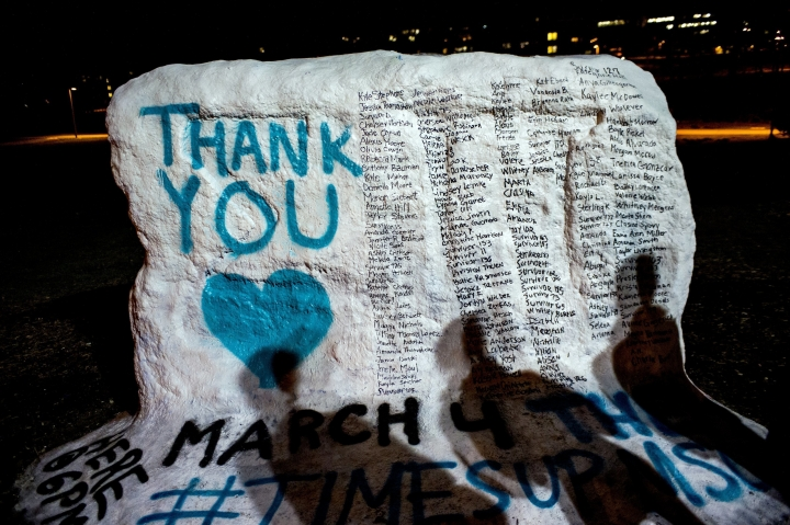"FILE - In this Jan. 26, 2018, file photo, the shadows of Michigan State University students appear on ""the rock"" in the university campus which was painted ""Thank You"" and includes the names of the women who gave victim impact statements during the Larry Nassar sexual assault sentencing hearing in East Lansing, Mich. Michigan State University announced Wednesday, May 16, 2018, that it has reached a $500 million settlement with hundreds of women and girls who say they were sexually assaulted by sports Nassar in the worst sex-abuse case in sports history. (Jake May/The Flint Journal-MLive.com via AP, File)"