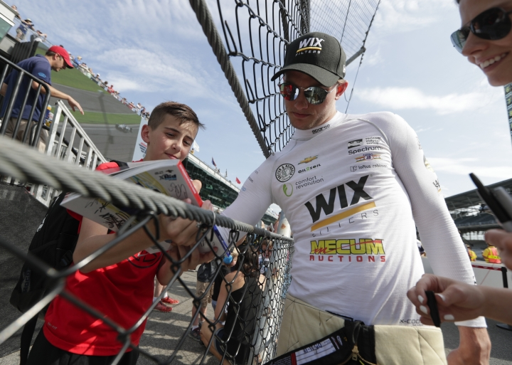Sage Karam signs an autograph on as he walks to his car during practice for the IndyCar Indianapolis 500 auto race at Indianapolis Motor Speedway in Indianapolis, Tuesday, May 15, 2018. (AP Photo/Michael Conroy)