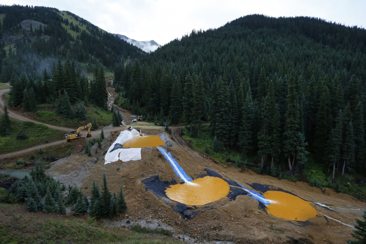 FILE - In this Aug. 12, 2015, file photo, water flows through a series of retention ponds built to contain and filter out heavy metals and chemicals from the Gold King Mine spill near Silverton, Colo. Environmental groups challenged the Trump administration in federal court Wednesday, May 16, 2018, over its rejection of an Obama-era proposal that would have required mining companies to prove they have enough money to clean up their pollution. (AP Photo/Brennan Linsley, File)