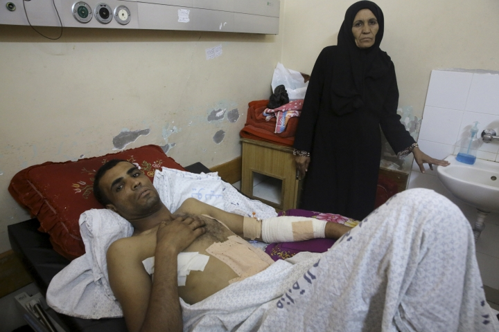 Marwan Shtewi, 32, lies on the bed while his mother's Fatma, stands near him at the surgery's ward of Shifa hospital in Gaza City, Wednesday, May 16, 2018. Shtewi was shot in his hand and abdomen by Israeli troops during a protest east of Gaza City on Monday. With few prospects and little to fear, Shtewi is among the crowds of young men who put themselves on the front lines of violent protests along the border with Israel, risking their lives in a weekly showdown meant to draw attention to the dire conditions of Gaza. (AP Photo/Adel Hana)