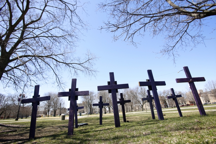 """Crosses representing victims of gun violence stand outside Collins Academy High School in Chicago's North Lawndale neighborhood on Thursday, April 19, 2018. The school is one of two campuses of North Lawndale College Prep High School. Both have Peace Warrior groups, which espouse the Rev. Dr. Martin Luther King Jr.'s """"Six Principles of Nonviolence"""" in an attempt to promote peace and interrupt conflict at their schools and in their city. North Lawndale is among the Chicago neighborhoods most impacted by gun violence. Most students know someone who's been killed. (AP Photo/Martha Irvine)"""