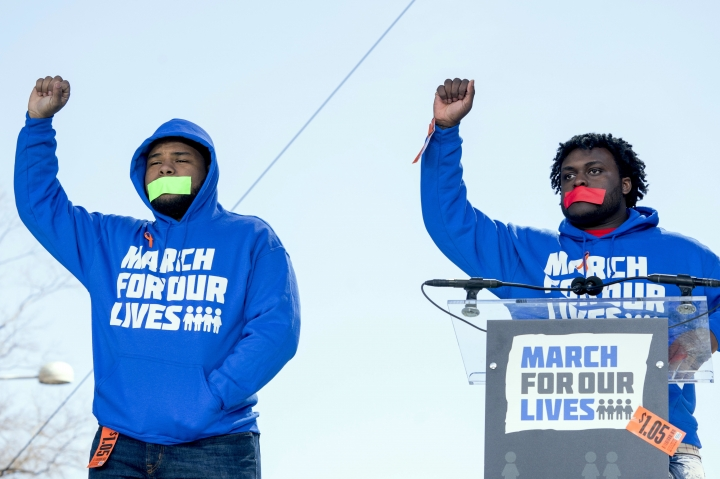 """FILE - In this Saturday, March 24, 2018 file photo, Alex King, right, and D'Angelo McDade, left, both graduating seniors at North Lawndale College Prep High School in Chicago raise their fists in the air as they arrive to speak during the """"March for Our Lives"""" rally in Washington. Both are Peace Warriors at their school and both have been impacted by gun violence. King lost a 16-year-nephew last year and McDade was shot in the leg. (AP Photo/Andrew Harnik)"""