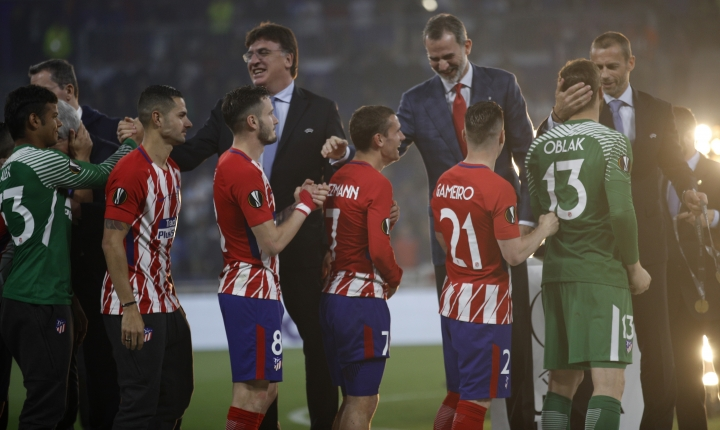 Spain's King Felipe, with red tie, congratulates Atletico's Antoine Griezmann after the team won the Europa League Final soccer match between Marseille and Atletico Madrid at the Stade de Lyon in Decines, outside Lyon, France, Wednesday, May 16, 2018. (AP Photo/Francois Mori)
