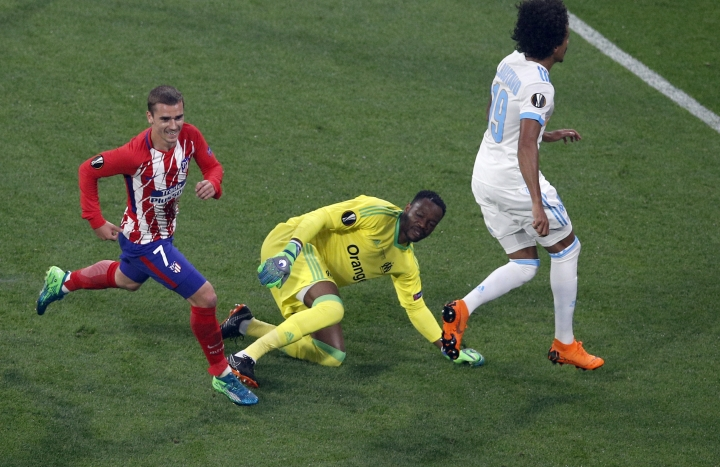 Atletico 's Antoine Griezmann, left, runs as Marseille's goalkeeper Steve Mandanda, center, looks on after Griezmann scored his side opening goal during the Europa League Final soccer match between Marseille and Atletico Madrid at the Stade de Lyon outside Lyon, France, Wednesday, May 16, 2018. (AP Photo/Christophe Ena)