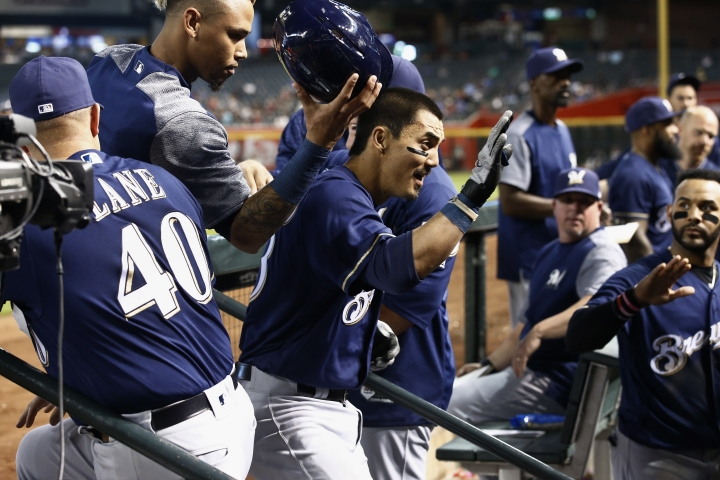 Milwaukee Brewers' Tyler Saladino, middle, celebrates his home run against the Arizona Diamondbacks with coach Jason Lane (40), Orlando Arcia, top left, Jonathan Villar, right, and other coaches and teammates during the fourth inning of a baseball game Wednesday, May 16, 2018, in Phoenix. (AP Photo/Ross D. Franklin)