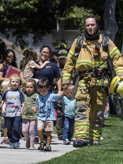 Firefighters and sheriff's deputies escort children from Academy on the Hill pre-k school in Aliso Viejo, Calif., on Tuesday, May 15, 2018, after a fatal explosion nearby. The blast involved a building under renovation but the cause was not immediately known, according to authorities. (Mindy Schauer/The Orange County Register/SCNG via AP)