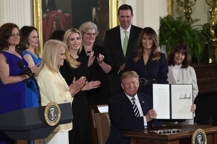 In this May 9, 2018 photo, President Donald Trump holds up an executive order he signed as he is surrounded by first lady Melania Trump, second from right, Karen Pence, right, White House counselor Kellyanne Conway, third from left, Ivanka Trump, fourth from left, and others during a celebration of military mothers and spouses event in the East Room of the White House in Washington. The House is set to give veterans more leeway to see doctors outside the Department of Veterans Affairs' health system. It's part of an effort to fulfill President Donald Trump's promise to expand private care for veterans. The long-awaited plan is set for a House vote later Wednesday. (AP Photo/Susan Walsh)