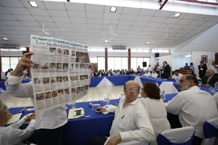 A woman holds up a newspaper that published images of some of the people who have died in the recent protests, interrupting Nicaragua's President Daniel Ortega at the opening of a national dialogue, in Managua, Nicaragua, Wednesday, May 16, 2018. Ortega sat down Wednesday to formally talk with opposition and civic groups for the first time since he returned to power in 2007. The dialogue comes after more than 60 people died amid a government crackdown on demonstrations against social security cuts. (AP Photo/Alfredo Zuniga)