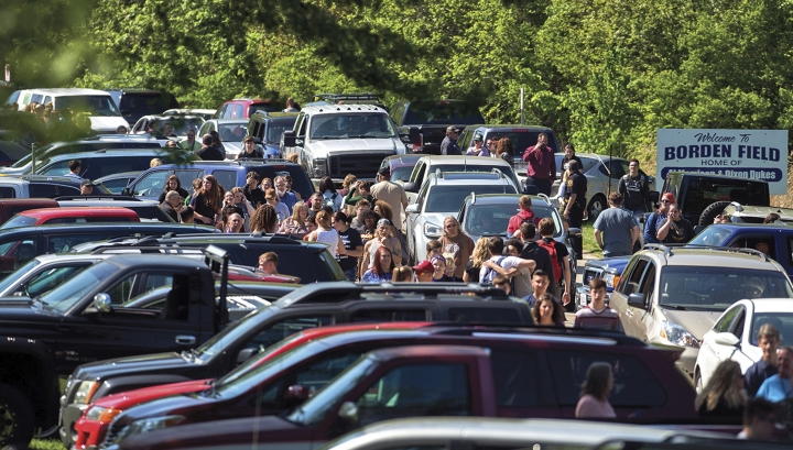 Parents wait down the road to meet their children following a shooting at Dixon High School Wednesday, May 16, 2018, in Dixon, Ill. A 19-year-old who showed up at his former high school in northern Illinois and opened fire on a police officer working there, was shot by the officer and taken into custody. The officer, who was not injured, was hailed a hero for his quick response protecting students and staff who had gathered at Dixon High School for a graduation rehearsal. (Alex T. Paschal/Sauk Valley Media via AP)