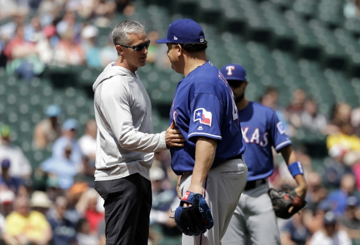 Texas Rangers trainer Kevin Harmon, left, touches the stomach of starting pitcher Bartolo Colon after Colon was hit with a ball hit by Seattle Mariners' Jean Segura during the fourth inning of a baseball game, Wednesday, May 16, 2018, in Seattle. Colon stayed in the game. The Rangers won 5-1. (AP Photo/Ted S. Warren)