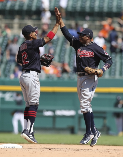 Cleveland Indians shortstop Francisco Lindor (12) and center fielder Rajai Davis celebrate the team's 6-0 win over the Detroit Tigers after a baseball game, Wednesday, May 16, 2018, in Detroit. (AP Photo/Carlos Osorio)