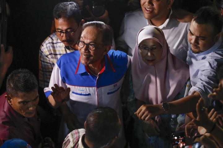 Malaysia's reformist icon Anwar Ibrahim, left, arrive with his wife Wan Azizah, right, at a rally in Petaling Jaya, Malaysia, Wednesday, May 16, 2018. Anwar has been freed from custody after receiving a pardon from the king, paving the way for a political comeback following his alliance's stunning election victory. (AP Photo/Vincent Thian)