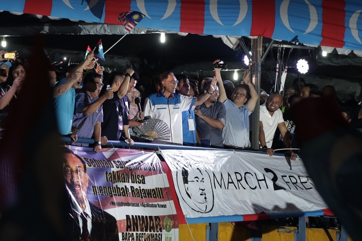 """Malaysia's reformist icon Anwar Ibrahim, center, gestures to his supporters during a rally in Petaling Jaya, Malaysia, Wednesday, May 16, 2018. Reformist icon Anwar Ibrahim celebrated a """"new dawn"""" for Malaysia after he was given a royal pardon and freed from custody Wednesday, transforming a political prisoner into a prime minister-in-waiting following his alliance's stunning election victory. (AP Photo/Andy Wong)"""