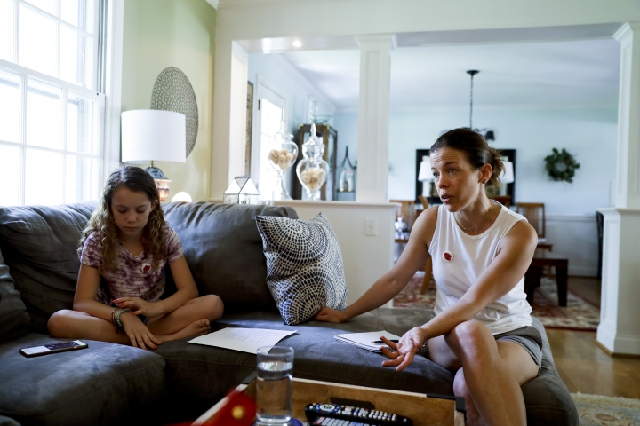 In this Thursday, May 3, 2018 photo, Sandy Nissenbaum, right, and her daughter, Nora Nissenbaum, 12, talk during an interview with The Associated Press in Wayne, Pa. The case of a suburban Philadelphia boy who was quietly allowed to return to class after being accused of making a shooting threat has thrown a spotlight on the hard decisions school authorities must make. Nora who says the boy bullied her has withdrawn from class for fear of him. (AP Photo/Matt Slocum)