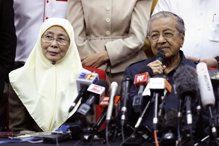 Malaysia Prime Minister Mahathir Mohamad, right, answers question from media as Wan Azizah, President of Justice Party, listening during a press conference in Petaling Jaya, Malaysia on Thursday, May 17, 2018. Mahathir, who was prime minister for 22 years until 2003, left the ruling party he once led to join a four-party coalition that scored a stunning victory in last week's elections. He has agreed to hand over power to jailed reformist leader Anwar Ibrahim but has not previously given any timing. (AP Photo/Vincent Thian)