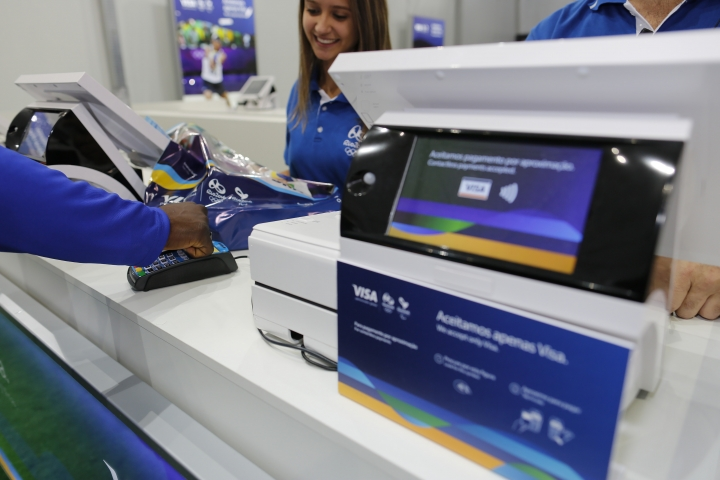 """In this June 30, 2016, image taken by AP Images for Visa, Team Visa athlete Popole Misenga uses his Visa payment ring at the Copacabana Megastore in Rio de Janeiro, Brazil. Payment networks and manufacturers are building payment functions into more devices — expanding your options as well as freeing up your hands. Connected """"smart"""" accessories such as watches, bands and rings travel lighter than a phone. To use, the wearer holds a wrist or hand up to a contactless payment terminal. Visa tested these devices at the 2016 Rio Olympics to demonstrate possibilities, says Mark Jamison, global head of innovation and design at Visa. (Leo Correa/AP Images for Visa)"""
