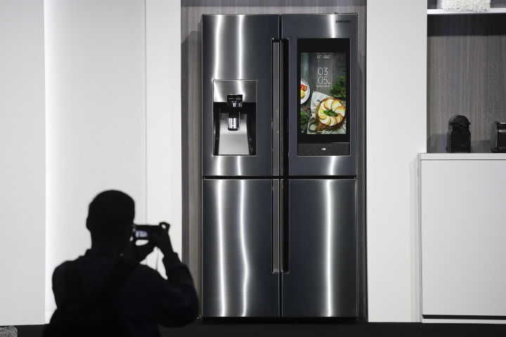 FILE- In this Jan. 8, 2018, file photo, an attendee takes pictures of the new Samsung Family Hub smart refrigerator during a news conference at CES International in Las Vegas. Payment networks and manufacturers are building payment functions into more devices — expanding your options as well as freeing up your hands. Samsung's Family Hub refrigerator, lets users order groceries from the Groceries by Mastercard app. (AP Photo/Jae C. Hong, File)