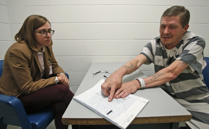 """In this Tuesday, May 1, 2018 photo, attorney Mary Frances Charlton, left, talks with inmate Richard Walls during an interview at the Richmond City Jail in Richmond, Va. A federal appeals court is weighing a challenge to a Virginia law that allows police to arrest """"habitual drunkards"""" such as Walls and send them to jail for up to a year for possessing alcohol. (AP Photo/Steve Helber)"""