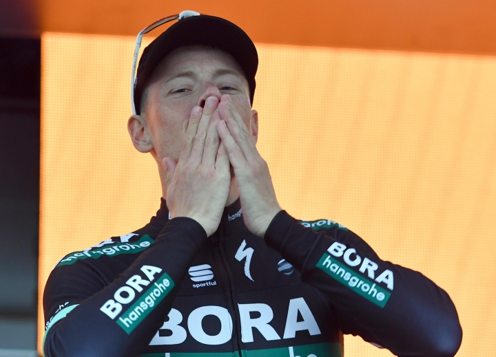 Sam Bennett of Ireland celebrates on the podium after winning the 12th stage of the Giro d'Italia cycling race from Osimo to Imola, Italy, Thursday, May 17, 2018. Bennett opened up his sprint a long way out to storm past Matej Mohoric and Carlos Betancur and claim his second victory of this Giro, as Britain's Simon Yates remained in the overall lead on Thursday. (Daniel Dal Zennaro/ANSA via AP)