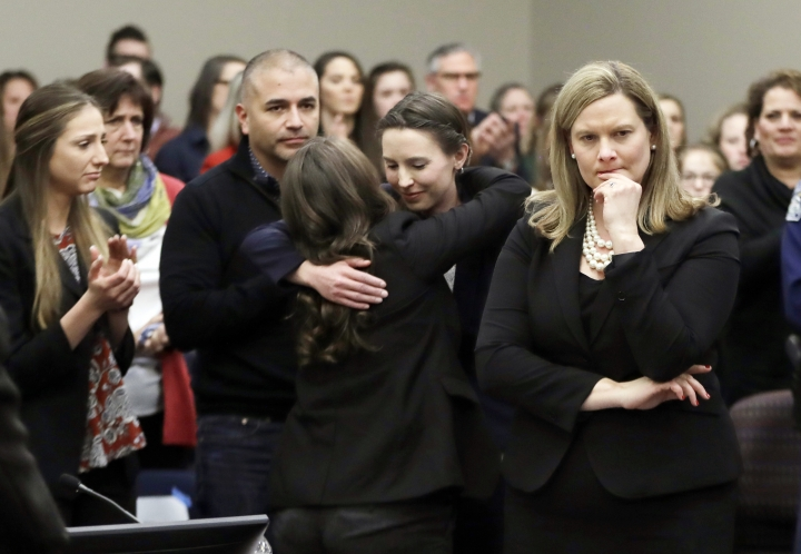 FILE - In this Jan. 24, 2018, file photo, former gymnast Rachael Denhollander, center, is hugged after giving her victim impact statement during the seventh day of Larry Nassar's sentencing hearing in Lansing, Mich. At right is Assistant Attorney General Angela Povilaitis. Michigan State University announced Wednesday, May 16, 2018, that it has reached a $500 million settlement with hundreds of women and girls who say they were sexually assaulted by sports Nassar in the worst sex-abuse case in sports history. (AP Photo/Carlos Osorio, File)