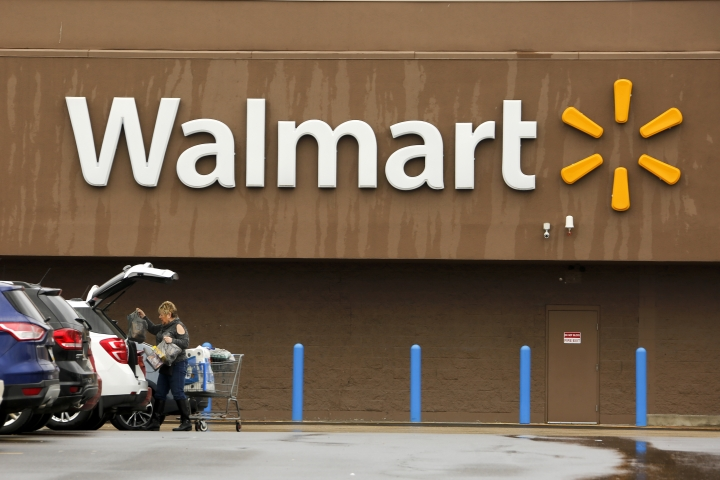 FILE- In this Feb. 22, 2018, file photo, a shopper loads her car after shopping at a Walmart in Pittsburgh. Walmart Inc. reports earnings on Thursday, May 17, 2018. (AP Photo/Gene J. Puskar, File)