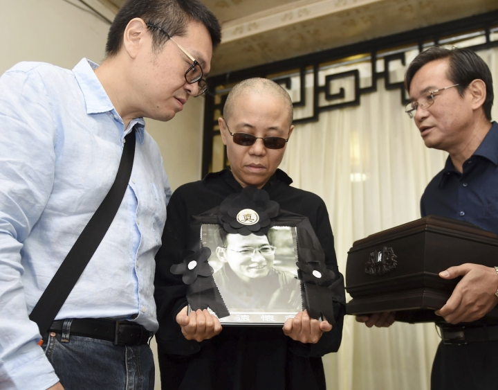 FILE - In this Saturday, July 15, 2017, file photo provided by the Shenyang Municipal Information Office, Liu Xia, center, wife of jailed Nobel Peace Prize winner and Chinese dissident Liu Xiaobo, holds a portrait of him during his funeral in Shenyang in northeastern China's Liaoning Province. China has rejected an appeal from dozens of writers and artists for the release from house arrest of Liu Xia, the widow of Nobel Peace Prize winner Liu Xiaobo. (Shenyang Municipal Information Office via AP, File)
