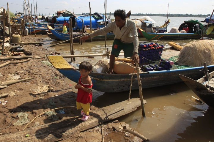 A man and grandchild prepares fishing nets at the Kbal Chroy village on the Mekong River bank near Phnom Penh, Cambodia, Thursday, May 17, 2018. A Chinese-backed plan for Cambodia to build the Mekong River's biggest dam would destroy fisheries that feed millions and worsen tensions with Vietnam, the downstream country with most to lose from dams on the waterway, according to a three-year study commissioned by the Cambodian government. (AP Photo/Heng Sinith)