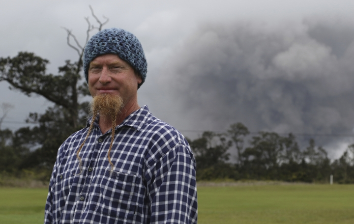 Joe Laceby, 47, of Volcano, Hawaii, watches as ash rises from the summit crater of Kilauea volcano, Thursday, May 17, 2018, in Volcano, Hawaii. Laceby said he has sealed up his home and has gas masks to protect himself from the volcanic gases and ash that is falling in the area. (AP Photo/Caleb Jones)