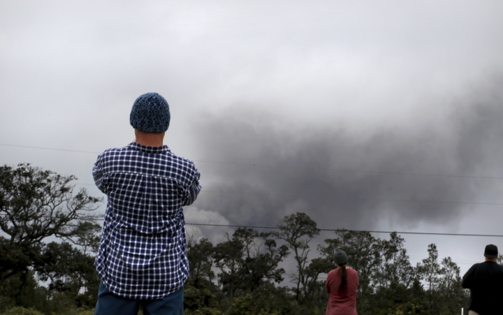 Joe Laceby, 47, of Volcano, Hawaii, watches as ash rises from the summit crater of Kilauea volcano, Thursday, May 17, 2018, in Volcano, Hawaii. Laceby said he has sealed up his home and has gas masks to protect himself from the volcanic gases ash that is falling in the area. (AP Photo/Caleb Jones)
