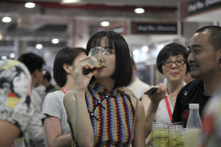 In this Thursday, May 17, 2018, photo, a woman drinks beer at the 2018 Craft Beer of China Exhibition in Shanghai. Hundreds of craft beer enthusiasts, investors and brewers are attending an exhibition in Shanghai dedicated to expanding the palette of Chinese consumers and promoting sales of high-end brews. (AP Photo/Fu Ting)