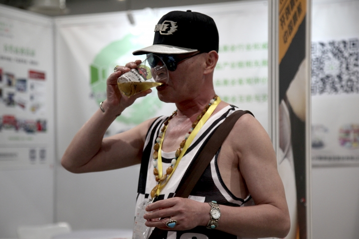 In this Thursday, May 17, 2018, photo, a man drinks beer while holding a second cup of beer at the 2018 Craft Beer of China Exhibition in Shanghai. Hundreds of craft beer enthusiasts, investors and brewers are attending an exhibition in Shanghai dedicated to expanding the palette of Chinese consumers and promoting sales of high-end brews. (AP Photo/Fu Ting)