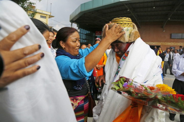 Friends and family offers a traditional hat to Nepalese veteran Sherpa guide, Kami Rita, 48, in Kathmandu, Nepal, Sunday, May 20, 2018. Rita, scaled Mount Everest on Wednesday morning May 16 for the 22nd time, setting the record for most climbs of the world's highest mountain, officials said. (AP Photo/Niranjan Shrestha)