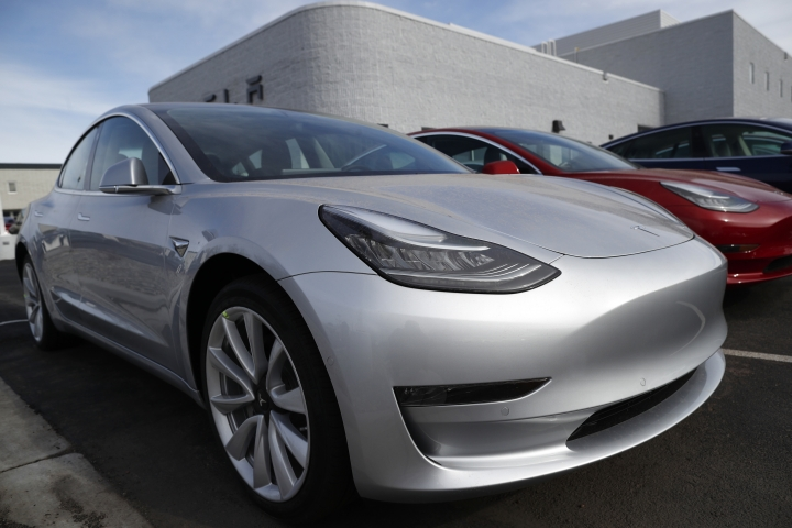 FILE- In this April 15, 2018, file photo unsold 2018 Model 3 Long Range versions sit on a Tesla dealer's lot in the south Denver suburb of Littleton, Colo. Long emergency stopping distances, difficult-to-use controls and a harsh ride stopped Tesla's Model 3 electric car from getting a recommended buy rating from Consumer Reports. The Model 3 is Tesla's first attempt to appeal to mass-market buyers. The car that starts at $35,000 but can run as high as $78,000 has been plagued by production delays. (AP Photo/David Zalubowski, File)