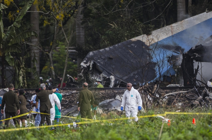 Forensic investigators sift through remains of a Boeing 737 that plummeted into a yuca field with more than 100 passengers on board, in Havana, Cuba, Friday, May 18, 2018. The Cuban airliner crashed just after takeoff from Havana's international airport. (AP Photo/Desmond Boylan)