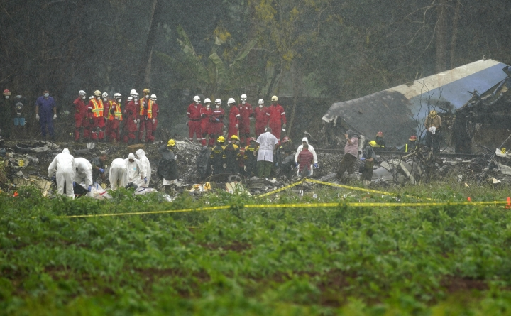 Rains begins to fall as rescue teams search through the wreckage site of Boeing 737 that plummeted into a yuca field with more than 100 passengers on board, in Havana, Cuba, Friday, May 18, 2018. The Cuban airliner crashed just after takeoff from Havana's international airport in Havana, Cuba. (AP Photo/Ramon Espinosa)