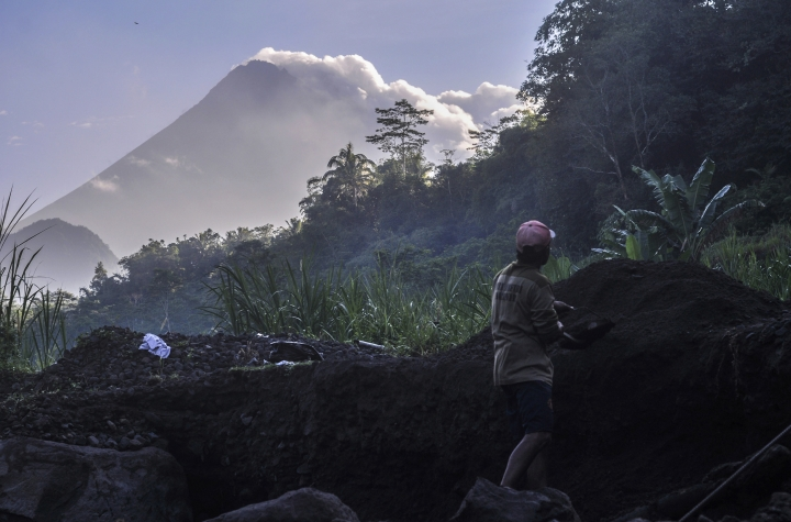 A man works at a sand mining site as Mount Merapi is seen in the background in Yogyakarta, Indonesia, Tuesday, May 22, 2018. Indonesian authorities raised the alert for the country's most volatile volcano, located on the densely populated island of Java, and ordered people within 3 kilometers (2 miles) to evacuate. (AP Photo/Slamet Riyadi)