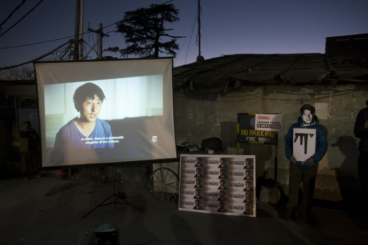 FILE - In this Jan. 8, 2018, file photo, an exile Tibetan wearing a mask in the likeness of 32-year-old Tashi Wangchuk, stands next to a screen projecting a New York Times video during a street protest demanding his release, in Dharmsala, India. China has sentenced the Tibetan language activist to five years in prison for inciting separatism after he appeared in a documentary video produced by The New York Times. Tashi Wangchuk had been detained in 2016, two months after the video and accompanying article were published. His lawyer says he plans to appeal. The case highlights the Chinese government's sensitivity to issues involving ethnic minorities. (AP Photo/Ashwini Bhatia, File)