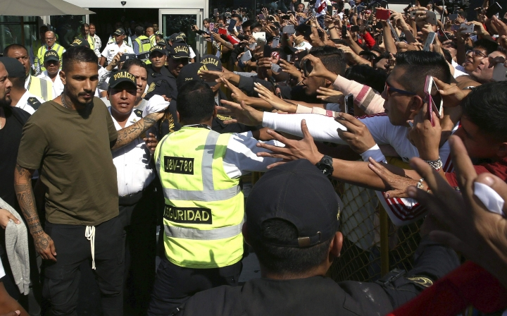 "Peru captain Paolo Guerrero, left, is greeted by fans as he arrives in Lima, Peru, Tuesday, May 15, 2018. The global footballers' union wants FIFA's help to review anti-doping rules after Guerrero was banned from the World Cup for a positive test for cocaine caused by contaminated tea. FIFPro says a 14-month ban barring the 34-year-old Guerrero from his World Cup debut is ""unfair and disproportionate."" (AP Photo/Martin Mejia)"