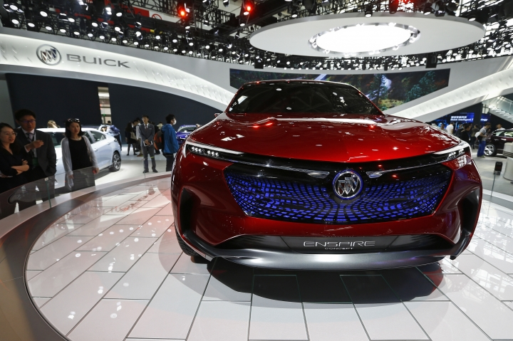 FILE - In this April 26, 2018, file photo, visitors look at a Buick Enspire concept car on display at the China Auto China in Beijing. China has announced it will reduce auto import duties effective July 1 following promises to buy more U.S. goods and end restrictions on foreign ownership in the industry. The Finance Ministry said Tuesday, May 22, 2018, that charges for many imported vehicles will be reduced from 25 percent to 15 percent. (AP Photo/Andy Wong, File)