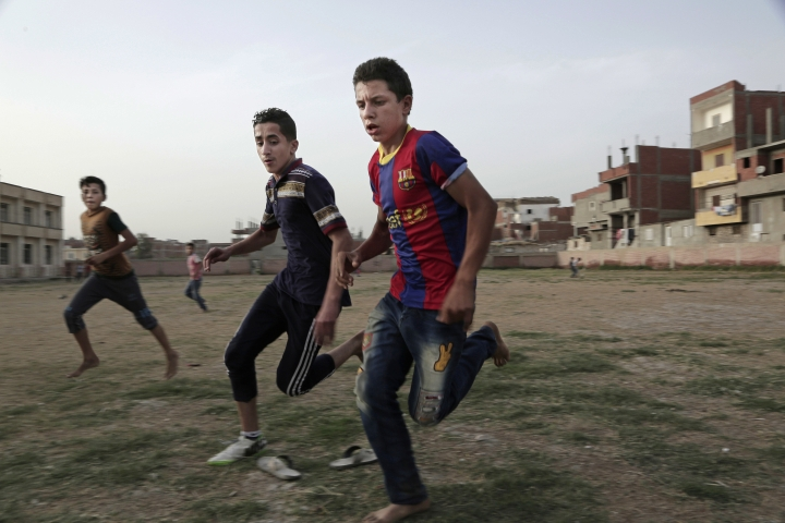 In this May 2, 2018 photo, boys play football at the sports and youth center, in Mohamed Salah's hometown Nile delta village of Nagrig, Egypt. Residents boast of how the Liverpool winger has poured millions of pounds into the village, with the beneficiaries' list including a school, a mosque, a youth center and a dialysis machine at a nearby hospital. His success as a footballer in Europe's most attractive league has inspired many parents in Nagrig to send their children to soccer academies in the hope that maybe one day they can emulate his success. (AP Photo/Nariman El-Mofty)