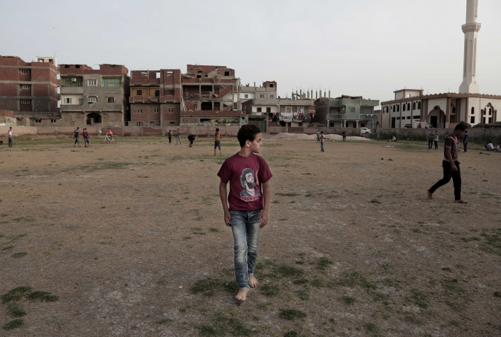 In this May 2, 2018 photo, boys play football at the sports and youth center in Mohamed Salah's hometown Nile delta village of Nagrig, Egypt. Residents boast of how the Liverpool winger has poured millions of pounds into the village, with the beneficiaries' list including a school, a mosque, a youth center and a dialysis machine at a nearby hospital. His success as a footballer in Europe's most attractive league has inspired many parents in Nagrig to send their children to soccer academies in the hope that maybe one day they can emulate his success. (AP Photo/Nariman El-Mofty)