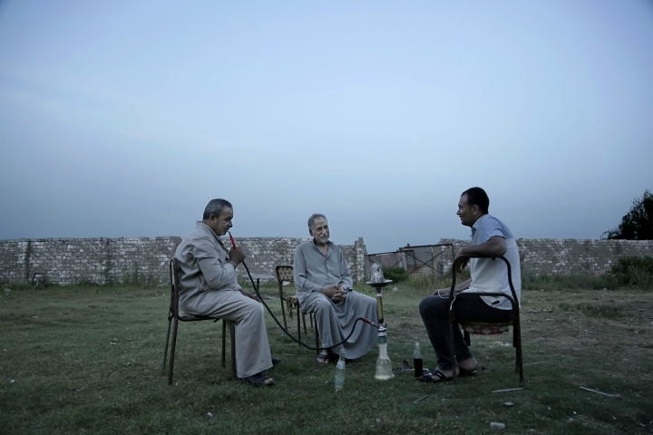 This May 2, 2018 photo, shows men talking near a cafe in Mohamed Salah's hometown Nile delta village of Nagrig, Egypt. Residents boast of how the Liverpool winger has poured millions of pounds into the village, with the beneficiaries' list including a school, a mosque, a youth center and a dialysis machine at a nearby hospital. His success as a footballer in Europe's most attractive league has inspired many parents in Nagrig to send their children to soccer academies in the hope that maybe one day they can emulate his success. (AP Photo/Nariman El-Mofty)