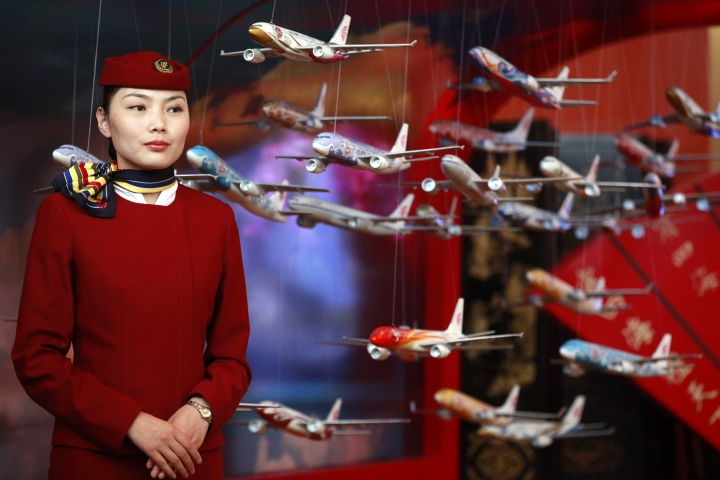 "FILE - In this June 12, 2012, file photo, an Air China flight attendant stands near model planes at the International Air Transport Association (IATA) 68th Annual General Meeting (AGM) and World Air Transport Summit in Beijing. Global airlines are obeying Beijing's demands to refer to Taiwan explicitly as a part of China, despite the White House's call this month to stand firm against such ""Orwellian nonsense."" (AP Photo/Ng Han Guan, File)"