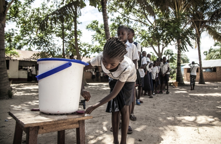 In this May 22, 2018 photo provided by UNICEF, schoolchildren wash their hands to help contain the Ebola outbreak before entering a classroom in the north-western city of Mbandaka, in Congo. Congo's health ministry announced six new confirmed Ebola cases and two new suspected cases Tuesday as vaccinations entered a second day in an effort to contain the deadly virus in the city of more than 1 million. (Mark Naftalin/UNICEF via AP)