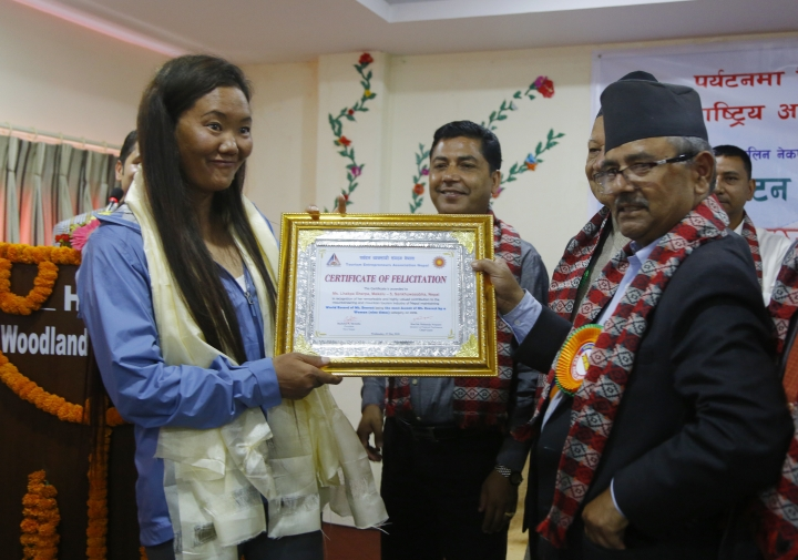 Nepalese woman climber Lhakpa Sherpa, left, is honored with an honorary certificate in Kathmandu, Nepal, Wednesday, May 23, 2018. Lhakpa Sherpa scaled the 8,850-meter (29,035-foot) peak last week, breaking her own record for the most climbs by a woman. (AP Photo/Niranjan Shrestha)